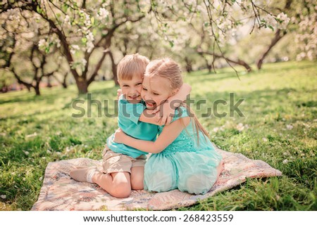 happy brother and sister are playing on blanket in spring apple garden - stock photo