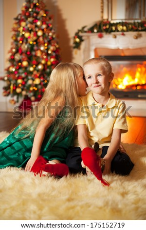 Happy brother and sister are playing on the floor near Christmas tree and fireplace. little friends enjoying New Year party, Christmastime holidays, best friends, happiness concept - stock photo