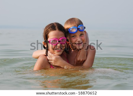 Happy brother and sister embrace each other in the water - stock photo
