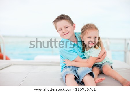 Happy brother and sister embracing each other - stock photo