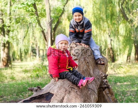 Happy brother and sister having fun in autumn park.Happy lifestyle kids - stock photo