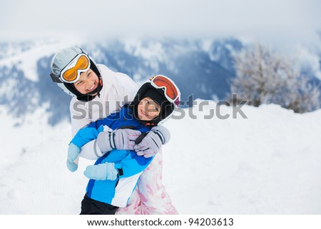 Happy brother and sister in ski goggles and helmets plaing on the downhill in wintertime - stock photo
