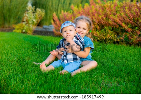 Happy brother and sister on green grass in spring park. Healthy lifestyles concept. - stock photo