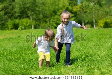 Happy brother and sister playing in the park bright summer day
