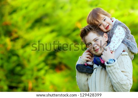 happy brother and sister playing outdoors - stock photo