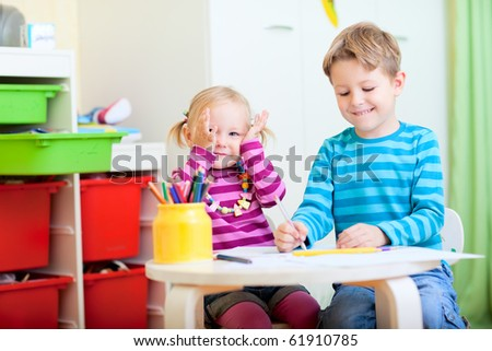 Happy brother and sister sitting together at table and drawing with pencils