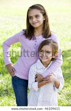 Happy brother and sister standing together outside on sunny day - stock photo