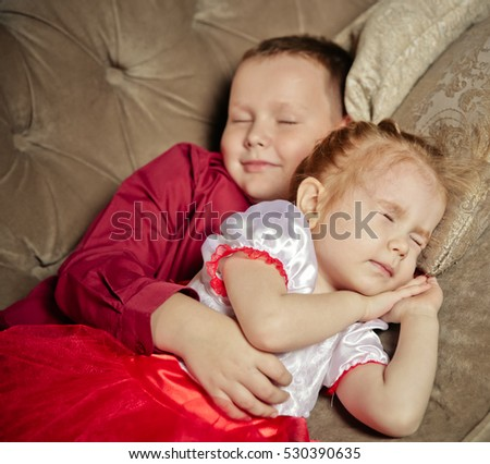 Happy brother and sister  wearing red skirt and pretty dress relaxing on the sofa