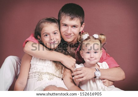 happy brother embracing his two sisters and posing in studio on brown background. Handsome teenager, cute toddler kid and lovely little girl in casual wear smiling. children's portrait. fashion shot - stock photo