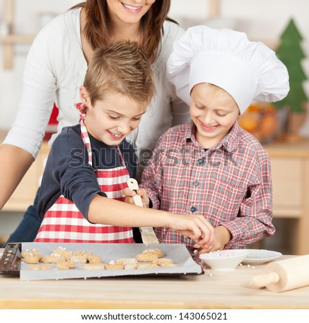 Happy brothers and mother baking cookies together at kitchen counter - stock photo