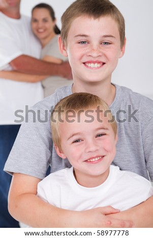 happy brothers hugging in front of parents - stock photo