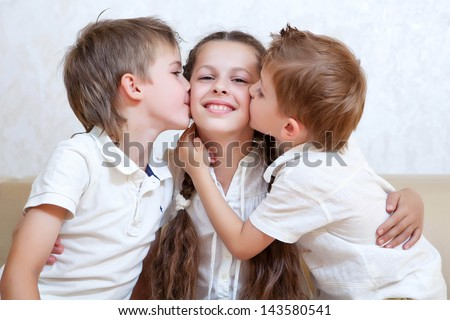happy brothers kiss the sister - stock photo