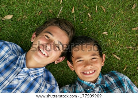 Happy brothers laying on the grass. - stock photo