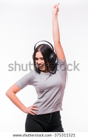 Happy brunet caucasian  girl listen dancing to music with headphones on a white background - stock photo