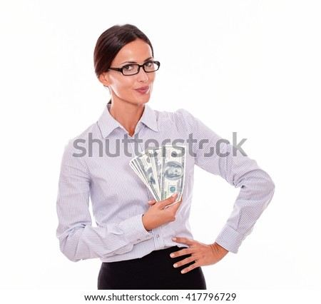 Happy brunette businesswoman holding money with a satisfied gesture and one hand to on her hip while wearing her straight hair back and a button down shirt from the waist up on a white background - stock photo