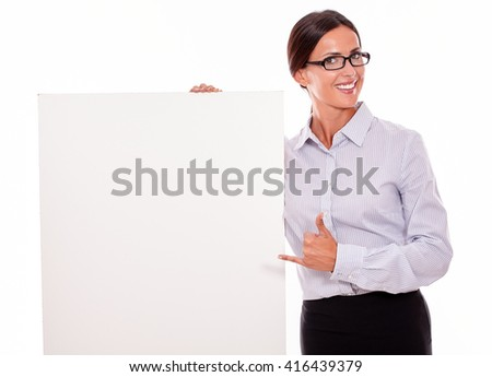 Happy brunette businesswoman looking at the camera, holding a placard with her toothy smile, wearing her straight hair tied back and a button down shirt, with a thumb up gesture, pointing at placard - stock photo