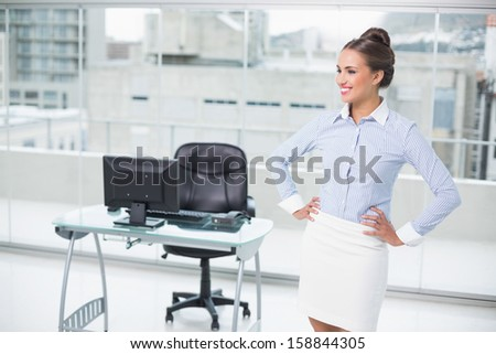 Happy brunette businesswoman standing hands on hips in bright office