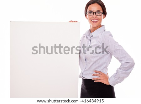 Happy brunette businesswoman with glasses looking at the camera, smiling, holding a placard, wearing her straight hair tied back and a button down shirt, gesturing with her left hand on her hip - stock photo