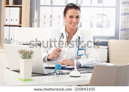 Happy brunette caucasian female doctor sitting at medical office desk in front of laptop computer, wearing glasses, stethoscope and lab coat. - stock photo