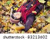 Happy brunette girl lying in autumn leaves. Outdoor. - stock photo