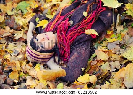 Happy brunette girl lying in autumn leaves. Outdoor. - stock photo