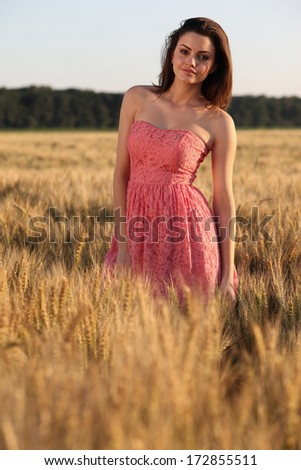 Happy brunette girl relaxing in the field at sunset .Fashion photo. - stock photo