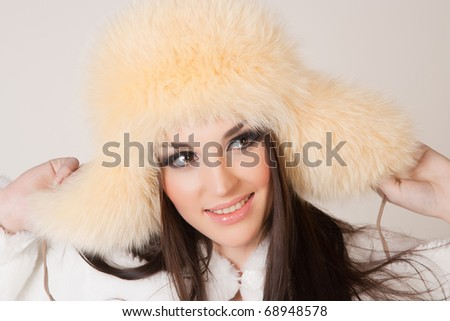 Happy brunette girl with furry hat, close up shot
