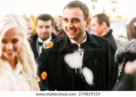 happy brunette groom and blonde bride goes under petals - stock photo