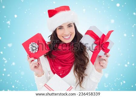 Happy brunette holding christmas gifts against blue vignette - stock photo