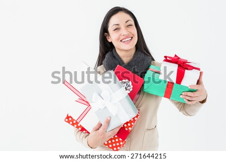 Happy brunette holding gifts on white background - stock photo