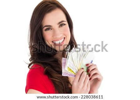 Happy brunette holding her cash money on white background - stock photo