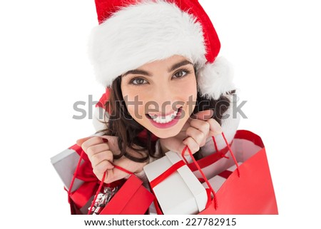 Happy brunette holding shopping bags full of gifts on white background