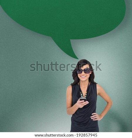 Happy brunette holding smartphone with speech bubble against blue background with vignette
