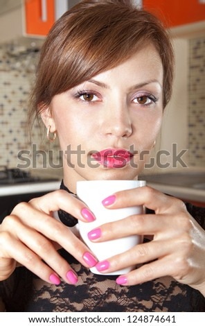 happy brunette in cafe at little table with cup of coffee - stock photo
