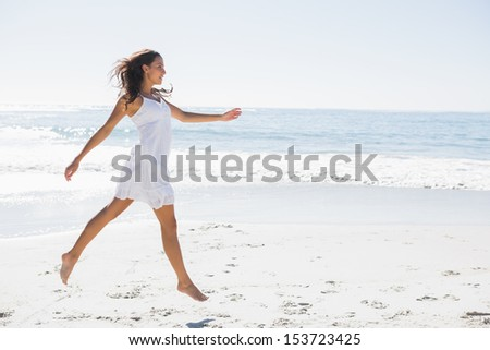 Happy brunette in white sun dress skipping on the sand on the beach - stock photo