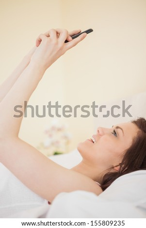 Happy brunette looking and using her phone lying on a bed in a bedroom - stock photo