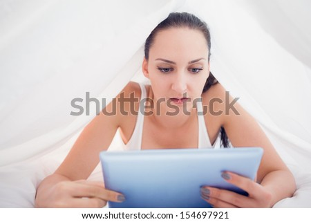Happy brunette lying under the sheets using her tablet pc in bedroom at home - stock photo
