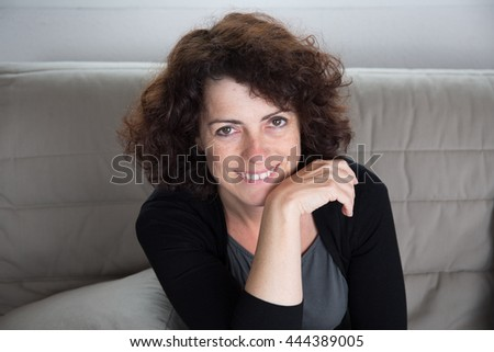 Happy brunette mature woman relaxing in sofa - stock photo
