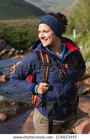 Happy brunette on a hike looking away in the countryside