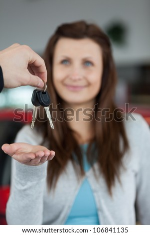 Happy brunette receiving car keys in a garage - stock photo
