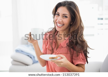 Happy brunette sitting on her sofa holding cup and saucer at home in the sitting room