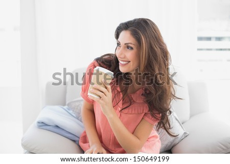 Happy brunette sitting on her sofa holding disposable cup at home in the sitting room - stock photo