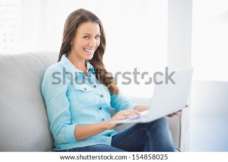 Happy brunette sitting on sofa in bright living room using laptop - stock photo