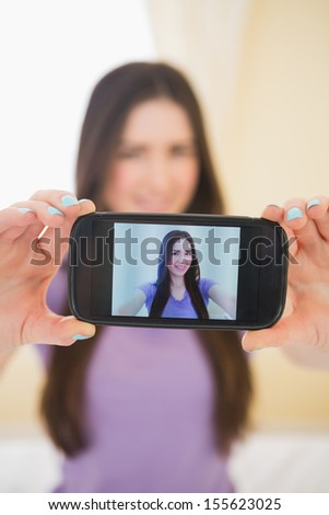 Happy brunette taking a photo of herself with her mobile phone in a bedroom - stock photo