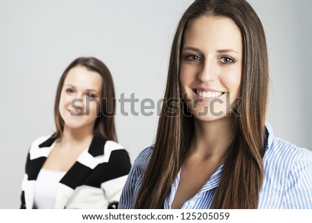 happy brunette teenager in front of other teenager - stock photo