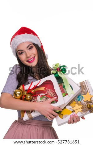 Happy brunette with her presents looks in the camera with a spread smile and holds gift boxes with sweets. Cute girl in red Santa's hat.
