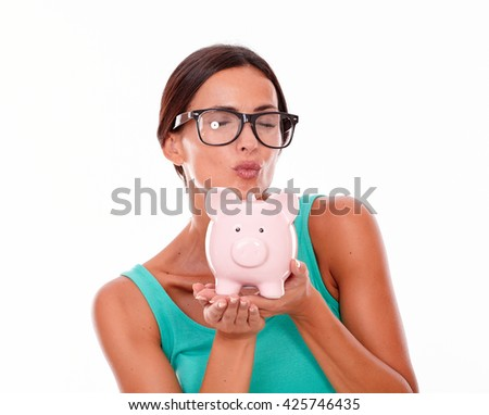 Happy brunette woman blowing a kiss at a pink piggy bank that she holds with both hands, wearing glasses and a tank top, isolated - stock photo