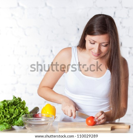 happy brunette woman cutting  fresh tomato over white brick wall - stock photo