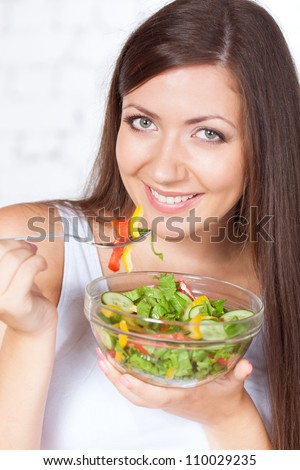 happy brunette woman eating fresh vegetable salad - stock photo