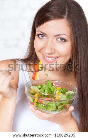 happy brunette woman eating fresh vegetable salad - stock photo
